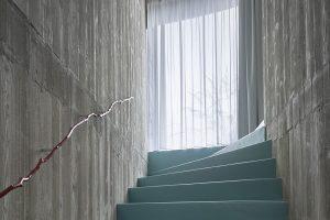Stěny schodiště jsou tvořené pohledovým betonem, do nějž je vetknuta struktura dřeva. Originální prvek vpodobě kovového zábradlí ve tvaru dřevěné větvičky nechybí ani zde. FOTO FILIP ŠLAPAL