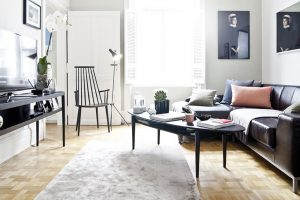 Obývací pokoj je úsporně zařízen. Velkou koženou pohovku doplňuje pouze elegantní kávový stolek, subtilní křeslo J110 od značky Hay atelevizní konzolová skříňka.FOTO WESTWING