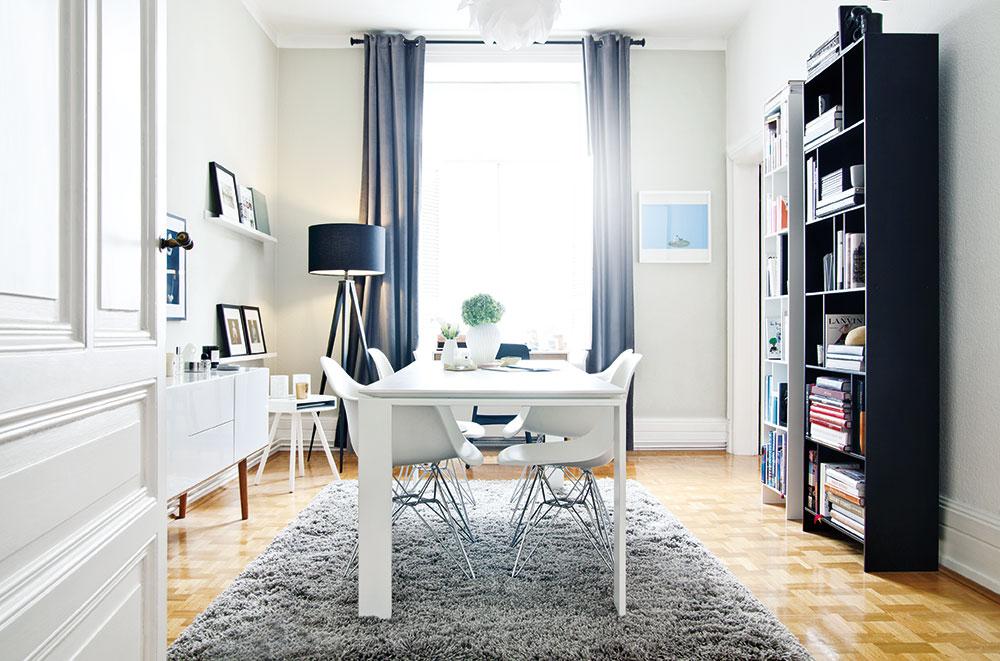 Jídelní stůl doplňují ikonické židle. Bílou kompozici pak doplňuje šedý koberec a tmavá knihovna. FOTO WESTWING