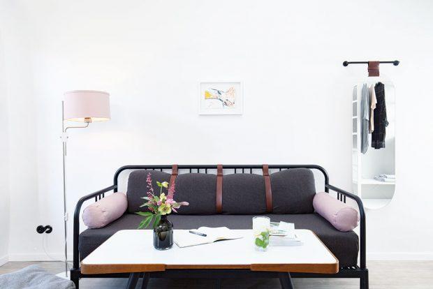Čistě bílá omítka kontrastuje s černými detaily i citlivým výběrem pastelových barevných odstínů, kterými je čalouněn jednoduše navržený sedací nábytek. FOTO JOSEF KUBÍČEK
