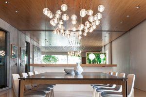 Pojítkem je dřevěný strop. Nad jídelním stolem jsou vněm instalovány oblíbené skleněné koule od značky Bocci.. FOTO RUI TEIXEIRA