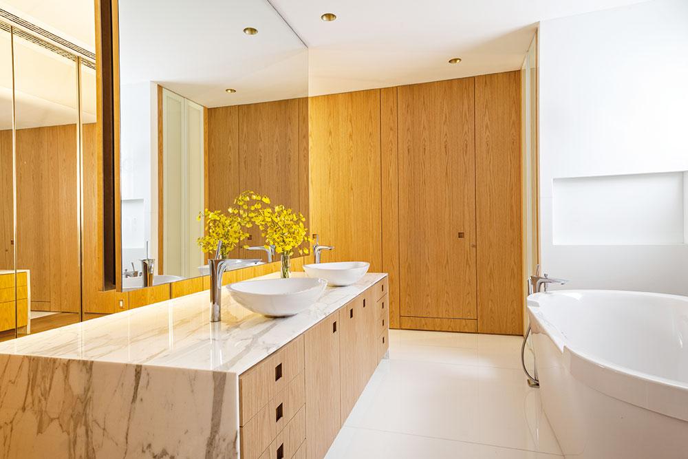 V koupelně je vedle masivního dřeva využit světlý mramor, který tvoří vrchní desku koupelnové skříňky. FOTO RUI TEIXEIRA
