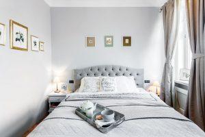 Ložnice je stejně jako celý byt laděná do jemných barev, kdy převažuje půvabná šedá. Stěny zdobí obrázky ve zlatých patinovaných rámečcích. FOTO FH STUDIO