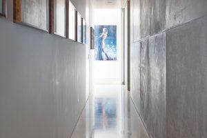 Spojovací chodba slouží zároveň jako galerie pro sbírku obrazů, kterou manželé vlastní. Obrazy jsou často obměňovány, atak architekt navrhl kjejich zavěšení systém ocelových lanek. FOTO RUI TEIXEIRA