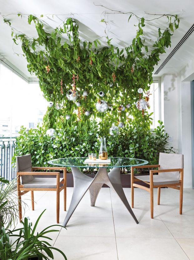 Terasa nabízí dostatek místa pro relaxaci apříjemný odpočinek uprostřed bujné zeleně. Mezi rostlinami jsou zavěšeny skleněné světelné koule od značky Bocci. FOTO RUI TEIXEIRA