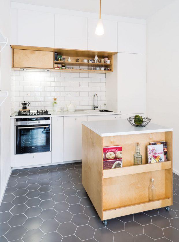 Šikovný kuchyňský ostrov na kolečkách je pohyblivý aje vněm prostor ina kuchařské knihy. Původní lampa nad pracovním pultem koresponduje svým charakterem sporcelánovým svítidlem umístěným nad jídelním stolem, které si majitelka bytu navrhla avyrobila sama. FOTO JURAJ STAROVECKÝ