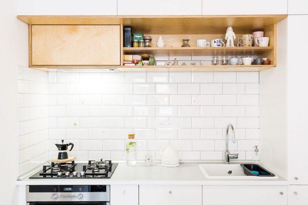 Kuchyňská linka je bílá shladkým povrchem auzavřenými skříňkami adoplňuje ji otevřená polička zpřekližky abílý obklad sautorskou dekorací. FOTO JURAJ STAROVECKÝ