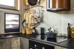 Kuchyně je vyvedena ve dřevě svýraznou kresbou. Uzavřené skříňky doplňují držáky zroxorových tyčí na kuchyňské náčiní. FOTO JH STUDIO