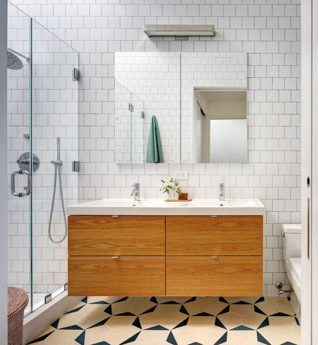 Hlavní koupelna je obložená bílým obkladem ageometrickou dlažbou. Dřevěný prvek ale nechybí. Zde je vpodobě čela umyvadlové skříňky. FOTO FRANCIS DZIKOWSKI