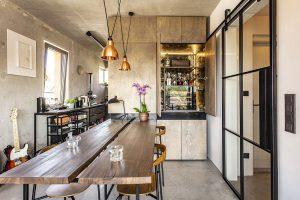 Masivní jídelní stůl zmodřínového dřeva je doplněn jídelními židlemi CH88 od Hanse J. Wegnera. Vna míru vyrobených skříních je spousta úložného prostoru, kde má majitel imalou kinotéku ahumidor na doutníky. FOTO JH STUDIO