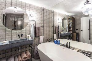 Ve vybavení koupelny se opět prosazuje kov abeton. Volně stojící vanu doplňuje betonové umyvadlo akovové tyče na zavěšení ručníků. FOTO JH STUDIO