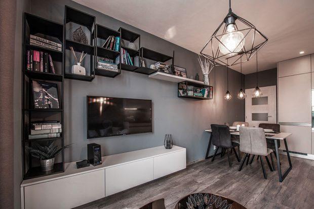 Kovové regály pokračují až k jídelnímu stolu a poskytují dostatek úložných prostor na knihy i dekorační předměty. FOTO: Radek Hensley