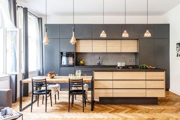 Kuchyň vyrobil na míru truhlář Jakub Heral. Majitelé si přáli kuchyňský ostrůvek splynovou varnou deskou avysouvací digestoří. Na ten navazuje masivní jídelní stůl smangového dřeva dovezený zIndie. Nad ním visí závěsné lampy ze showroomu Claro. FOTO JH STUDIO