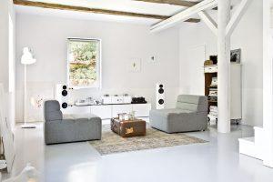 Přízemí domu tvoří jeden centrální prostor, jehož součástí je iobývací zóna. Jednoduché střídmé pohovky doplňuje starý lodní kufr, který slouží jako konferenční stolek. Bílé stěny ibílá betonová podlaha tvoří všemu krásný světlý rám. FOTO WESTWING