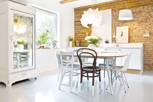 Vkuchyni je přiznaná zeď, která kontrastuje sbělostným ajakoby nadýchaným vybavením kuchyně. Masivní vitrína se zrcadlovými dveřmi vtipně odráží dění ustolu. FOTO WESTWING