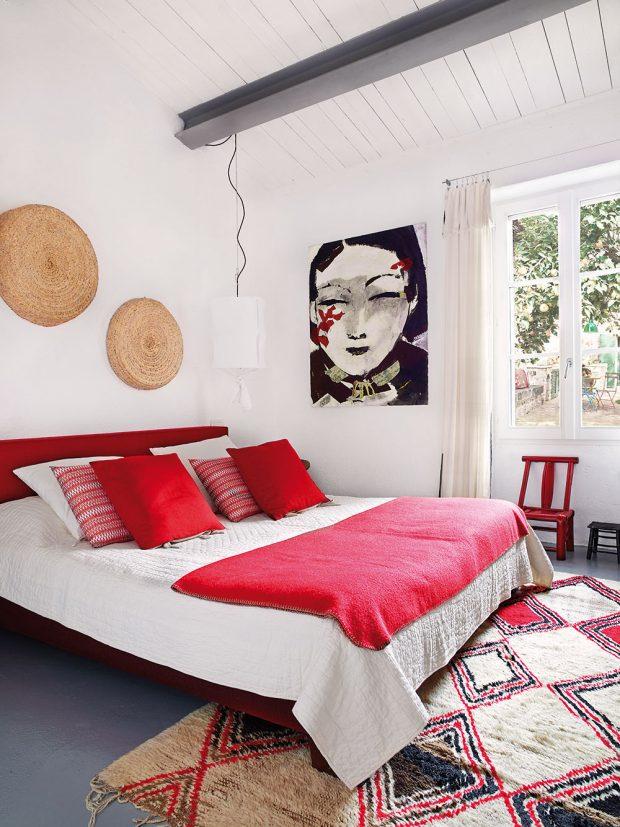 Hlavní ložnici charakterizuje přímočará barevná kombinace červené, bílé ašedé, jednoduché materiály akosmopolitní design. Bílou prošívanou deku na posteli si přivezl majitel zIndie, deka zčervené vlny je zAustrálie, polštáře jsou italské. Košíky, které zdobí stěnu nad postelí, pocházejí zMaroka amalba je od stejného umělce jako obraz vobýváku. FOTO KRISTIAN SEPTIMIUS KRO