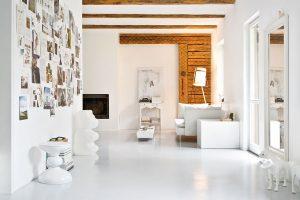 Hrubě opracované trámové stropy azachované trámoví na stěně kontrastují sdokonalou bělostí celoplošné betonové podlahy. Prostor je vzdušný, světlý aopravdu lákavý. FOTO WESTWING