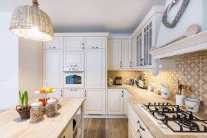 """Prostorná kuchyně se nachází vpřízemí domu aplynule přechází do jídelního koutu, kterému dominuje velký oválný stůl ažidle zmasivního dřeva. Ratanové asmaltované doplňky dodávají prostoru to správné """"teplo domova"""". FOTO MIRO POCHYBA"""
