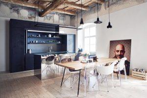 Kuchyně je vyvedena včerném betonu akuchyňský ostrůvek je obložený zrcadlovými plechy, vnichž se odráží celý zbytek prostoru. FOTO ZDENĚK BUCHLÁK