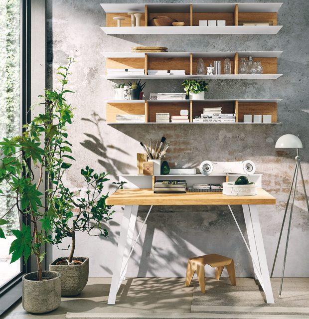 Naoko odřená stěna, pracovní stůl skovovými nohami, vysoká stojací lampa ašedá barva jako základ vytvoří tu pravou industriální atmosféru vkaždé pracovně.