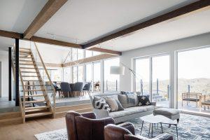 Otevřený prostor je navržen tak, aby co nejlépe plnil společenskou funkci. Obývací část spohovkou akřesly je otři schody snížena aidíky dřevu na podlaze avelkému vlněnému koberci působí útulně. FOTO ADRIEN WILLIAMS