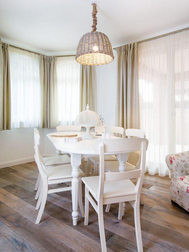 Prosvětlená jídelna smasivním stolem přímo vybízí ktomu, abyste se usadili avychutnali si velkorysé stolování, jak se patří. Záclony azávěsy jsou vcelém domě šité na míru, aby ladily sostatním zařízením. FOTO MIRO POCHYBA