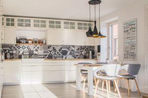 Bílý nábytek v jednoduchých a čistých tvarech doplňují prvky přírodního dřeva. FOTO finalfin