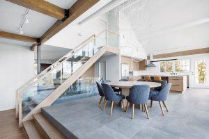 Vyvýšený jídelní akuchyňský prostor spojuje se vstupní chodbou keramická dlažba. Masivní jídelní stůl je vyrobený na míru adoplněný osmi čalouněnými židlemi. Drátěná svítidla jsou nejen praktická, ale ivelmi zdobná. FOTO ADRIEN WILLIAMS