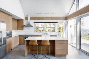 Jednoduše řešená kuchyň je vyvedena vpřírodním dřevu. Pracovní ostrůvek doplňují dvě kožené barovky skovovou konstrukcí. FOTO ADRIEN WILLIAMS