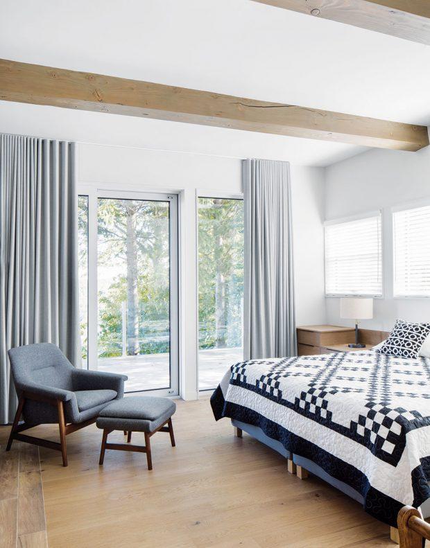 Ložnice svýstupem na terasu je zařízena ve stejném barevném duchu jako zbytek domu. Výraznějším prvkem je černobílý pléd. FOTO ADRIEN WILLIAMS