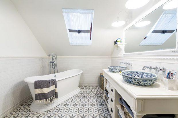 Královská koupelna vpatře svolně stojící vanou advěma umyvadly je prostorná asvětlá. Pocit útulnosti jí dodávají ispeciálně navržené záclony na střešní okna. FOTO MIRO POCHYBA