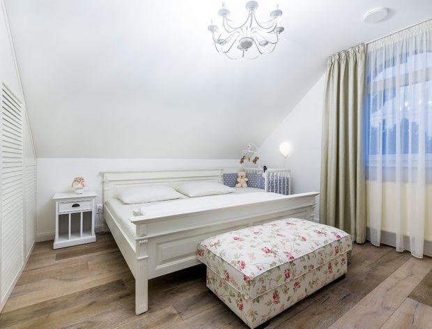 Bílá masivní postel apodnožka sromantickým květinovým potahem tvoří kontrast sdřevěnou podlahou, vše to působí útulně ačistě. Dojem elegantní ložnice na anglický způsob se vydařil. FOTO MIRO POCHYBA