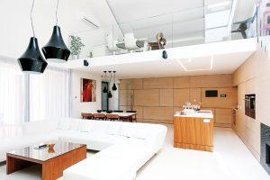 Ve vzdušném prostoru, který je vpřímém kontaktu svenkovní terasou, je situován otevřený obývací pokoj spojený skuchyní ajídelnou. Velkorysá denní zóna zúročuje ivýškové členění stavby – pod asymetrickou střechou má místo galerie spracovnou. FOTO JOZEF BARINKA