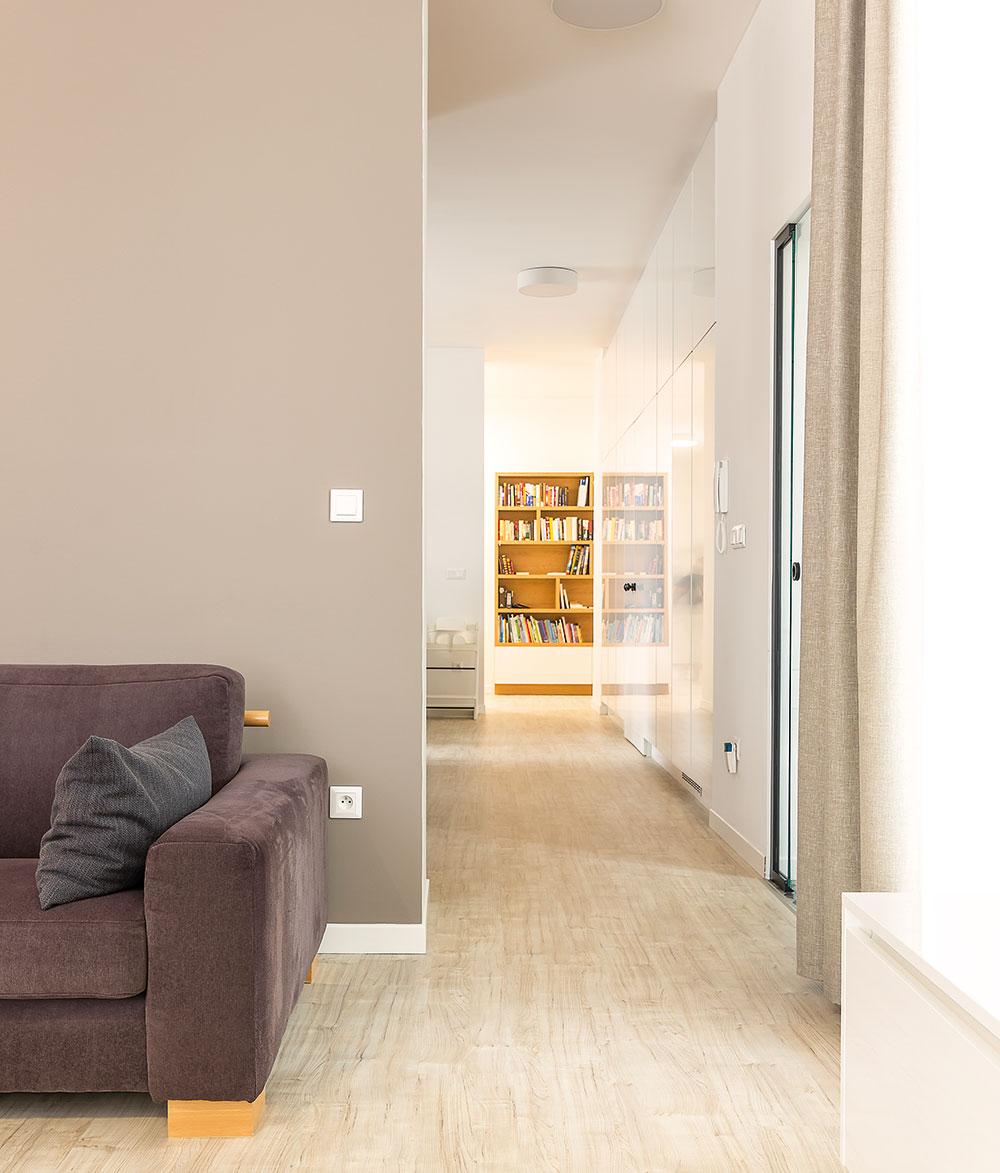 Průhled přes celou denní část bytu až do noční zóny opticky propojil rozlehlý prostor. Původní nosné zdi totiž nedovolily otevřít ho tak, jak by si majitelé přáli. FOTO MIRO POCHYBA