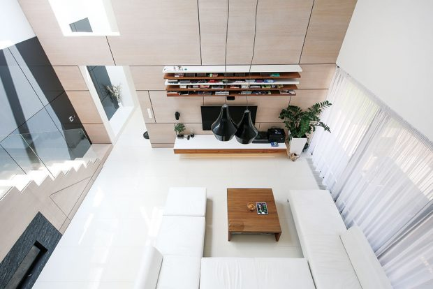 Minimalistickému interiéru dominuje bílá barva – bílá je slinutá keramická dlažba ivětšina stěn, bílá se objevuje ina nábytku atextiliích. Harmonicky ji doplňují dva druhy dřeva – bělený dub aořech, znichž je vyhotoven obklad stěn anábytek. FOTO JOZEF BARINKA