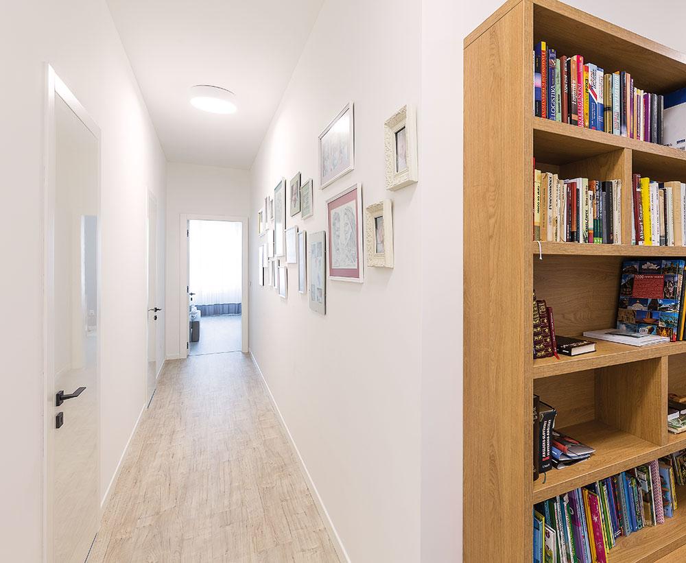 Rodinné fotografie změnily chodbu vedoucí krodičovské ložnici na malou galerii. Na tom, že působí příjemně, mají svůj podíl isvítidla, která poskytují silné bílé světlo podobné dennímu, ataké světlé barvy všech povrchů včetně dveří, které dodávají prostoru vzdušnost. FOTO MIRO POCHYBA