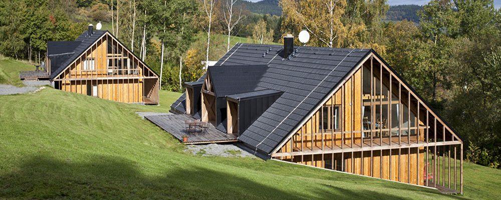 Vedle sebe vyrostly dvě moderní dřevěné chaty podle starých principů