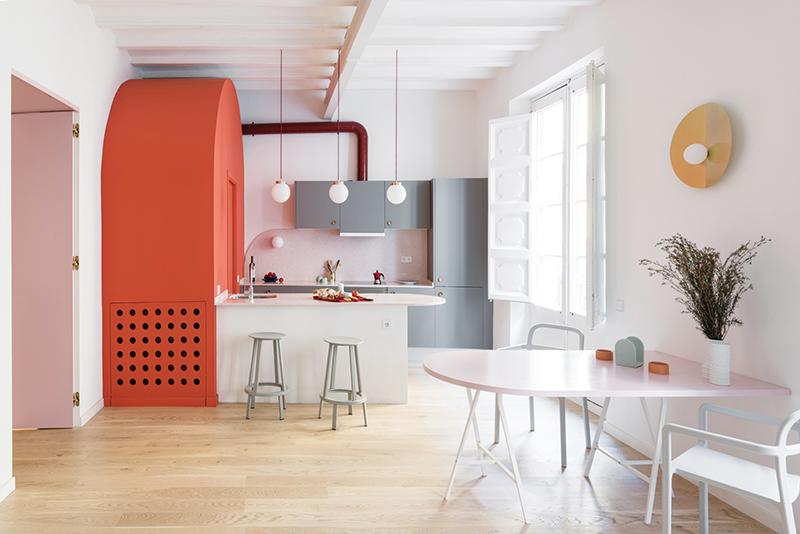 Kuchyně a jídelní zóna jsou propojeny s obývacím pokojem. Obloukový útvar v korálové barvě ukrývá koupelnu pro hosty, kterou majitelka bezpodmínečně požadovala a kvůli které nechtěli architekti ubírat prostoru na velkorysé otevřenosti. Přišli proto s velmi originálním řešením. Výraznou barvu pak doplňuje neutrální šedá na kuchyňské lince a světle růžové terazzo na desce jídelního stolu, desce kuchyňského ostrůvku a obkladu za pracovní plochou.