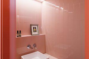 Koupelnu pro hosty umístili architekti do obloukovitého boxu, který dosahuje téměř ke stropu, ale neomezuje otevřený prostor.