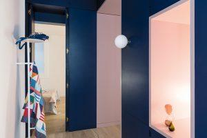 Dělicí tmavomodrý box s růžovými průhledy a vstupy navrhli architekti a vyrobila firma FustHeri. Věšák Norm koupila majitelka od značky Menu.