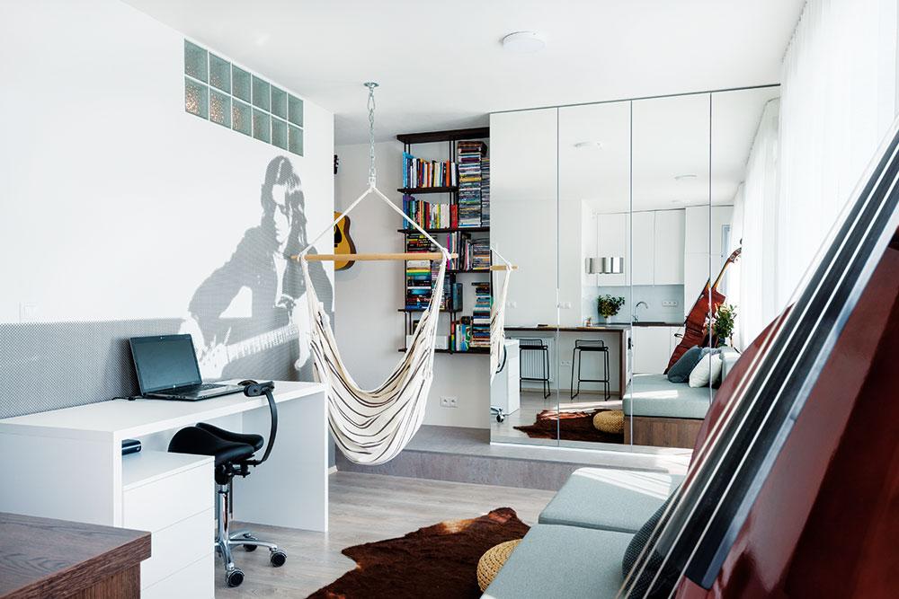 5 POKOJŮ NA 33 m². Na malou plochu se podařilo designérkám vtěsnat kuchyň, jídelní kout, obývací pokoj, ložnici ipracovnu. Místo si zde našla dokonce ivysněná houpačka, ve které si majitel rád přečte knihu. FOTO VENTURA PICTURES