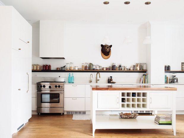 Kuchyňská sestava je jednoduchá vbílé barvě avytváří ten nejlepší základ pro hru sdoplňky na dlouhé otevřené polici. Zpřípadné nepozornosti vás vytrhne medvědí hlava, která cení zuby na stěně nad pracovní deskou. FOTO ÉLÈNE LEVASSEUR