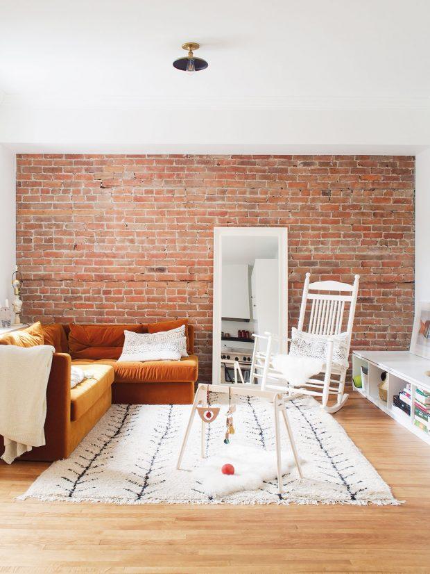 Obývací zóna je zařízena velmi jednoduše avelmi funkčně. Odhalené cihly jedné ze zdí jsou připomínkou viktoriánské architektury. Rohovou pohovku vcihlové barvě doplňuje dřevěné houpací křeslo asvětlý koberec. FOTO ÉLÈNE LEVASSEUR