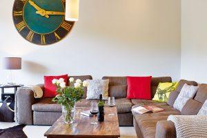 Vpodstatě jednoduše zařízený interiér činí zajímavým vtipné dekorace, jako například záměrně velké abarevné nástěnné hodiny, závěsné osvětlení astarožitný stůl. FOTO UNIQUE HOME STAYS UK