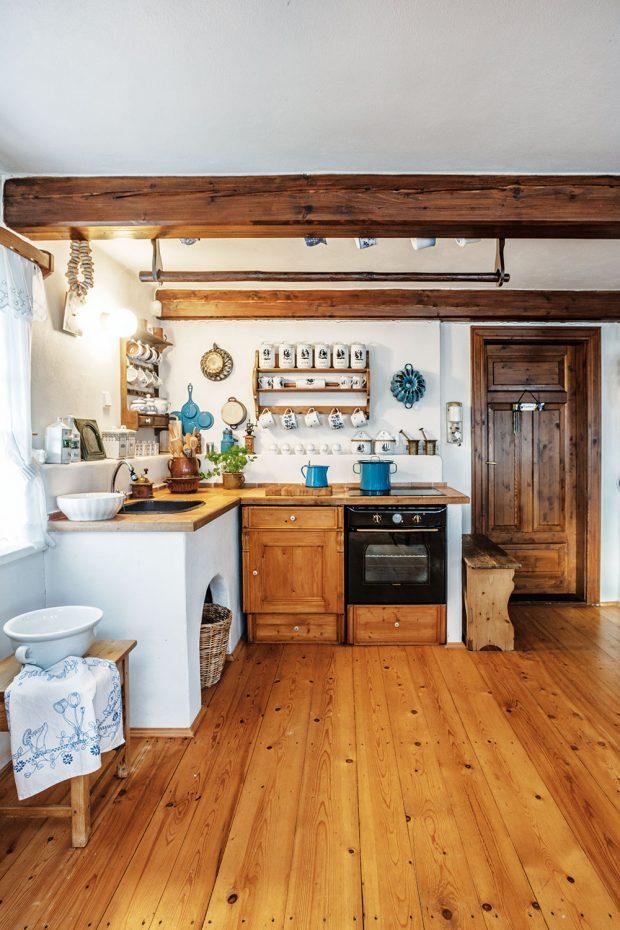 Moderní spotřebiče nemají vkuchyni místo. Jedinou výjimkou je indukční deska, ale majitelka stejně ráda vaří na kamnech. Lednice apračka jsou vprovozní místnosti anekazí dojem starých časů. FOTO JIŘÍ HURT