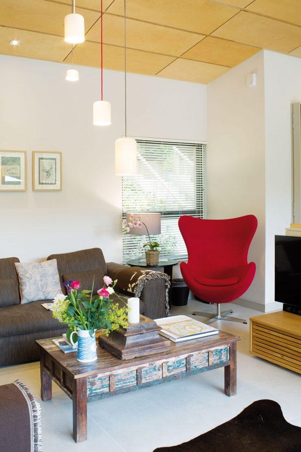 Červené čtenářské křeslo je výrazným solitérem aspolu sdalšími červenými prvky dodává interiéru šťávu. FOTO UNIQUE HOME STAYS UK