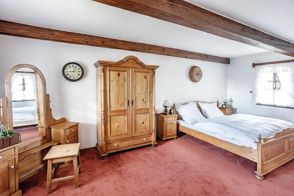 Ložnice se chlubí nejen krásnou dřevěnou postelí svyřezávaným čelem, ale itoaletním stolkem arobustní šatní skříní. FOTO JIŘÍ HURT