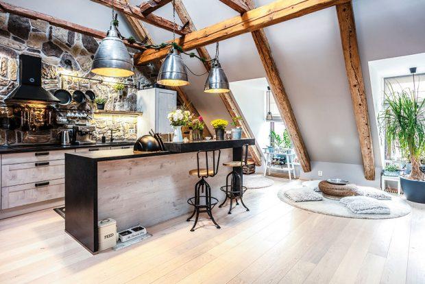 Otevřenému společnému prostoru dominuje kuchyň sbarovým ostrůvkem, který zastupuje jídelní stůl. Celá stěna je obložená kamenem, který ladí skrásnými původními trámy. Nábytek se kloní kindustriálnímu stylu, který zjemňují romantické dekorace. FOTO JIŘÍ HURT