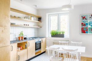 """Majitelé se nebáli otevřených úložných prostor a nechtěli digestoř. I díky tomu působí kuchyň propojená s obývacím pokojem subtilně a vlastně """"nekuchyňsky"""". Bílý obklad je kvůli snadné udržovatelnosti vyspárován šedou spárovačkou. FOTO BENEDIKT MARKEL ADOMINIK KUČERA"""