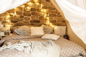 Romanina ložnice je umístěna nad kuchyní astěna vzáhlaví postele je také obložena kameny. Bílé závěsy přispívají kpocitu bezpečného hnízda. FOTO JIŘÍ HURT